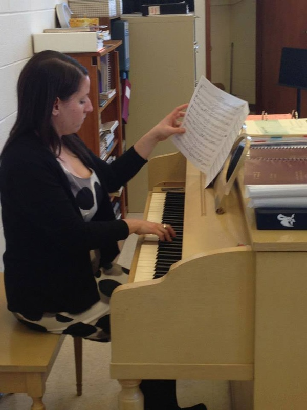 Kelly Rizzo-McLain looks over music at choir practice.
