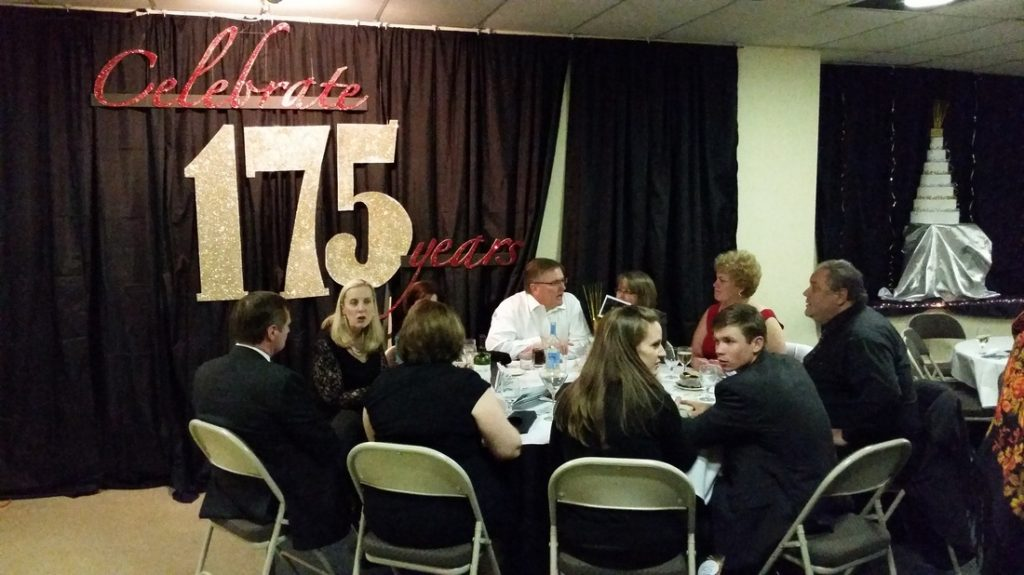 People talking at table at the 175th anniversary of the church