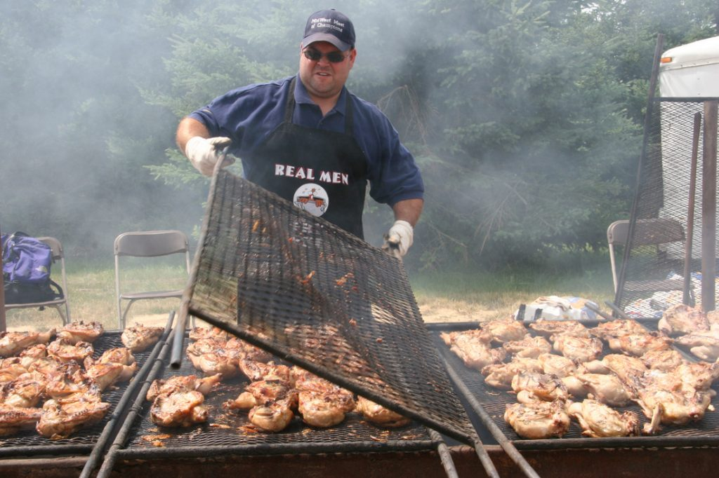 Man lifting up grilling grate