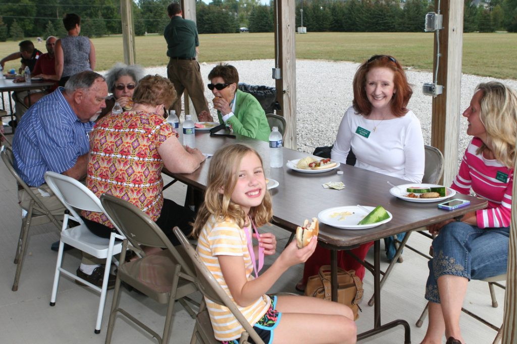 Administrative assistant Catherine Wolfe (2d from right) at parish picnic with former Parish Council president Ann Blakeslee.