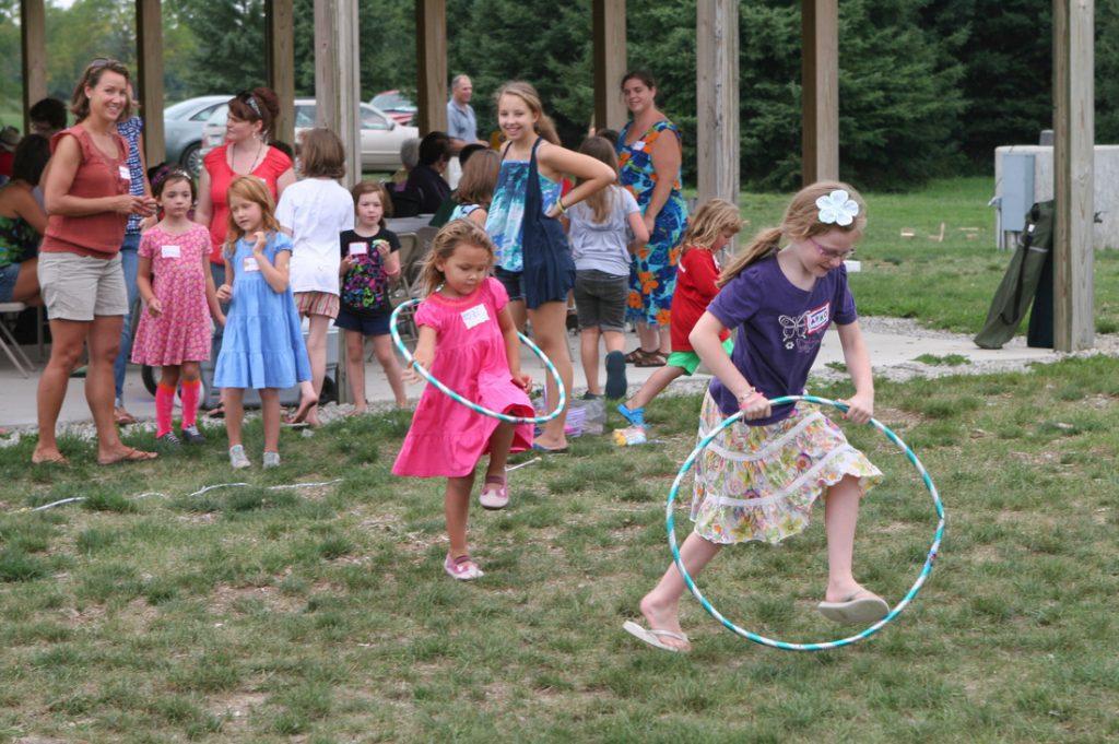 Girls running with hula hoops
