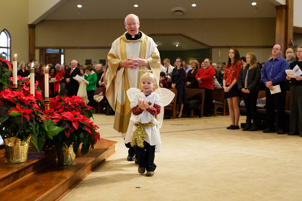 The littlest angel carries the baby Jesus to the manger on Christmas Eve.